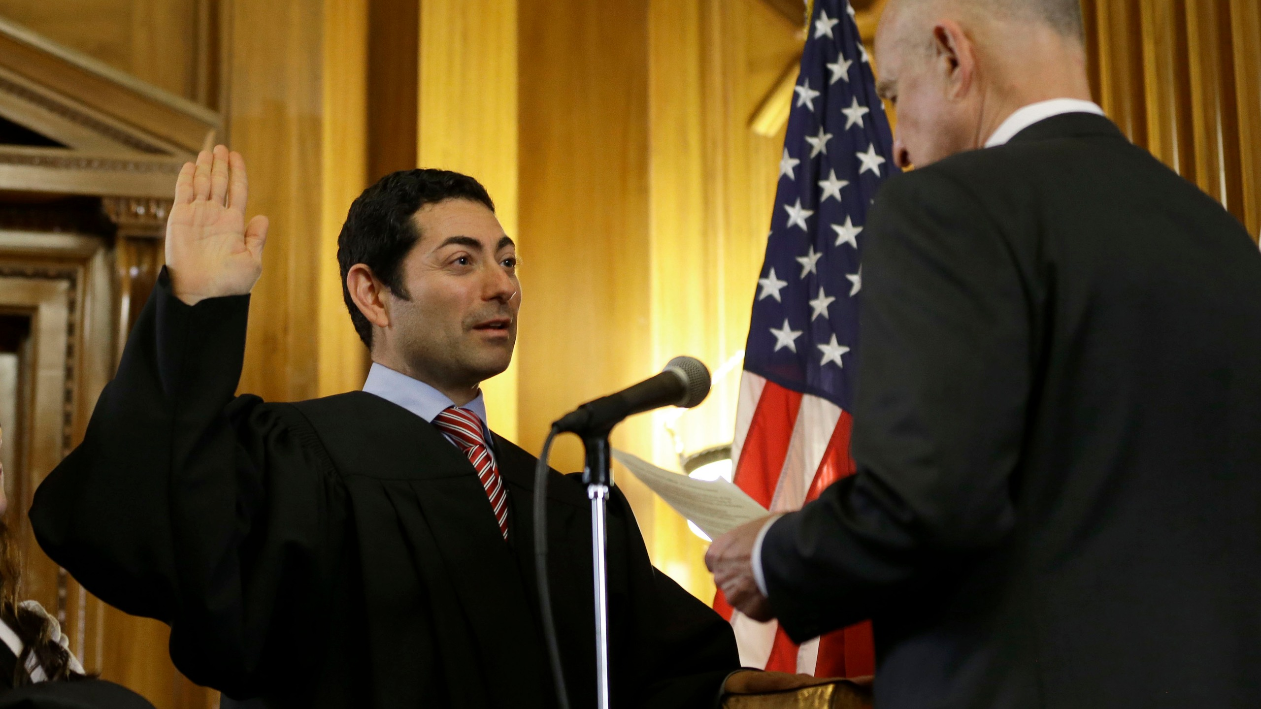 In this Jan. 5, 2015 file photo Mariano-Florentino Cuellar, left, is sworn in as an associate justice to the California Supreme Court by Gov. Jerry Brown during an inauguration ceremony in Sacramento. (Rich Pedroncelli/Associated Press)