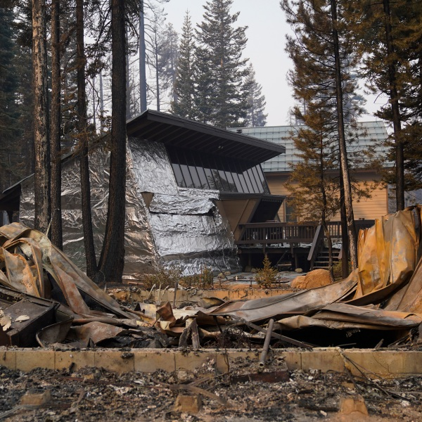 In this Sept. 2, 2021 file photo a cabin partially covered in fire-resistant material stands behind a property destroyed in the Caldor Fire in Twin Bridges, Calif. (AP Photo/Jae C. Hong,File)