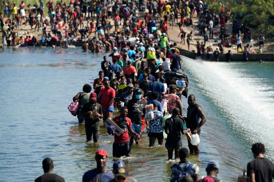 Haitian migrants use a dam to cross to and from the United States from Mexico on Sept. 17, 2021, in Del Rio, Texas. (Eric Gay / Associated Press)