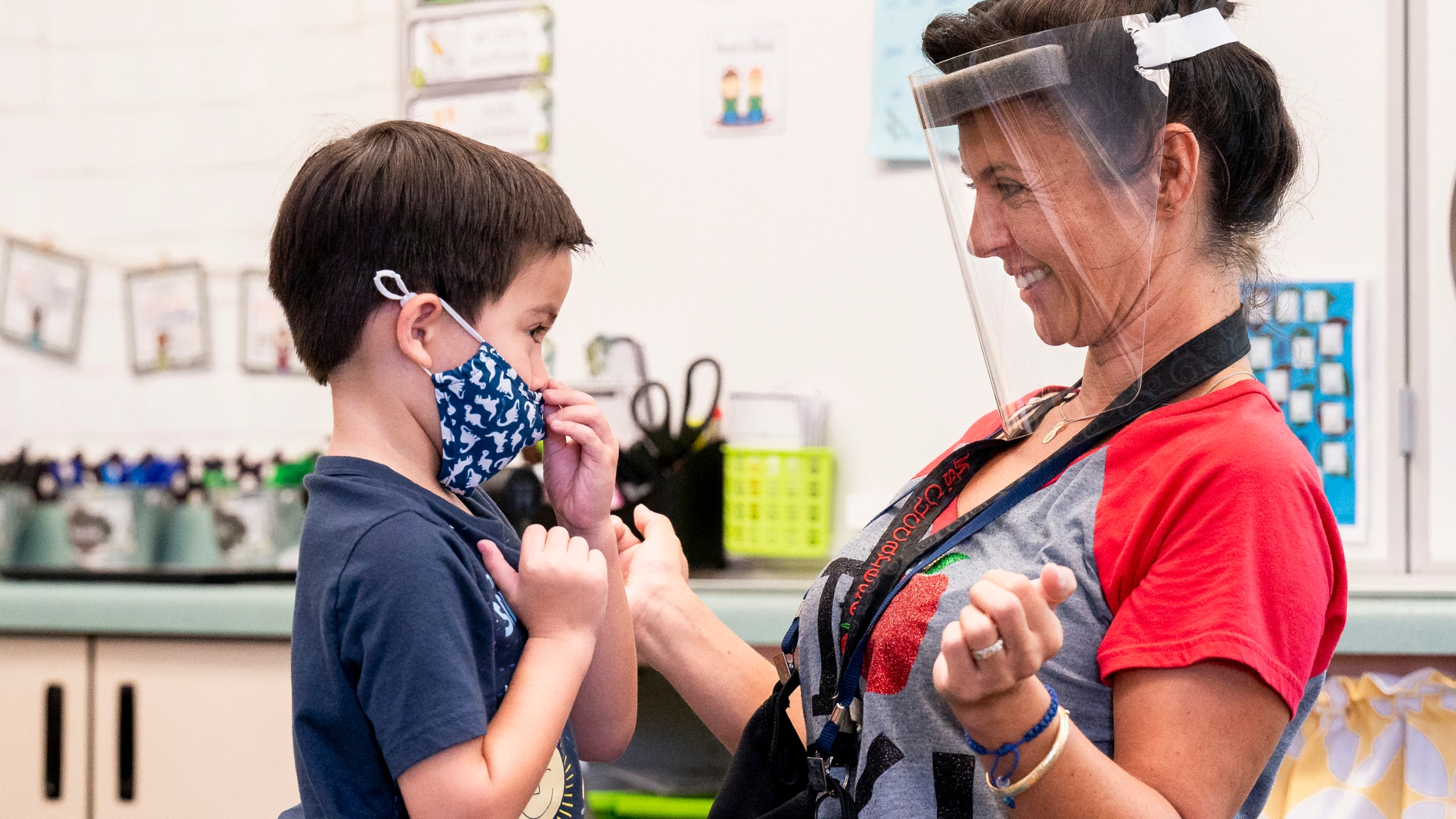 In this Aug. 12, 2021, file photo, a student gets help with his mask from transitional kindergarten teacher Annette Cuccarese during the first day of classes at Tustin Ranch Elementary School in Tustin, Calif. Now that California schools have welcomed students back to in-person learning, they face a new challenge: A shortage of teachers and all other staff, the likes of which some districts say they've never seen. (Paul Bersebach/The Orange County Register via AP, File)