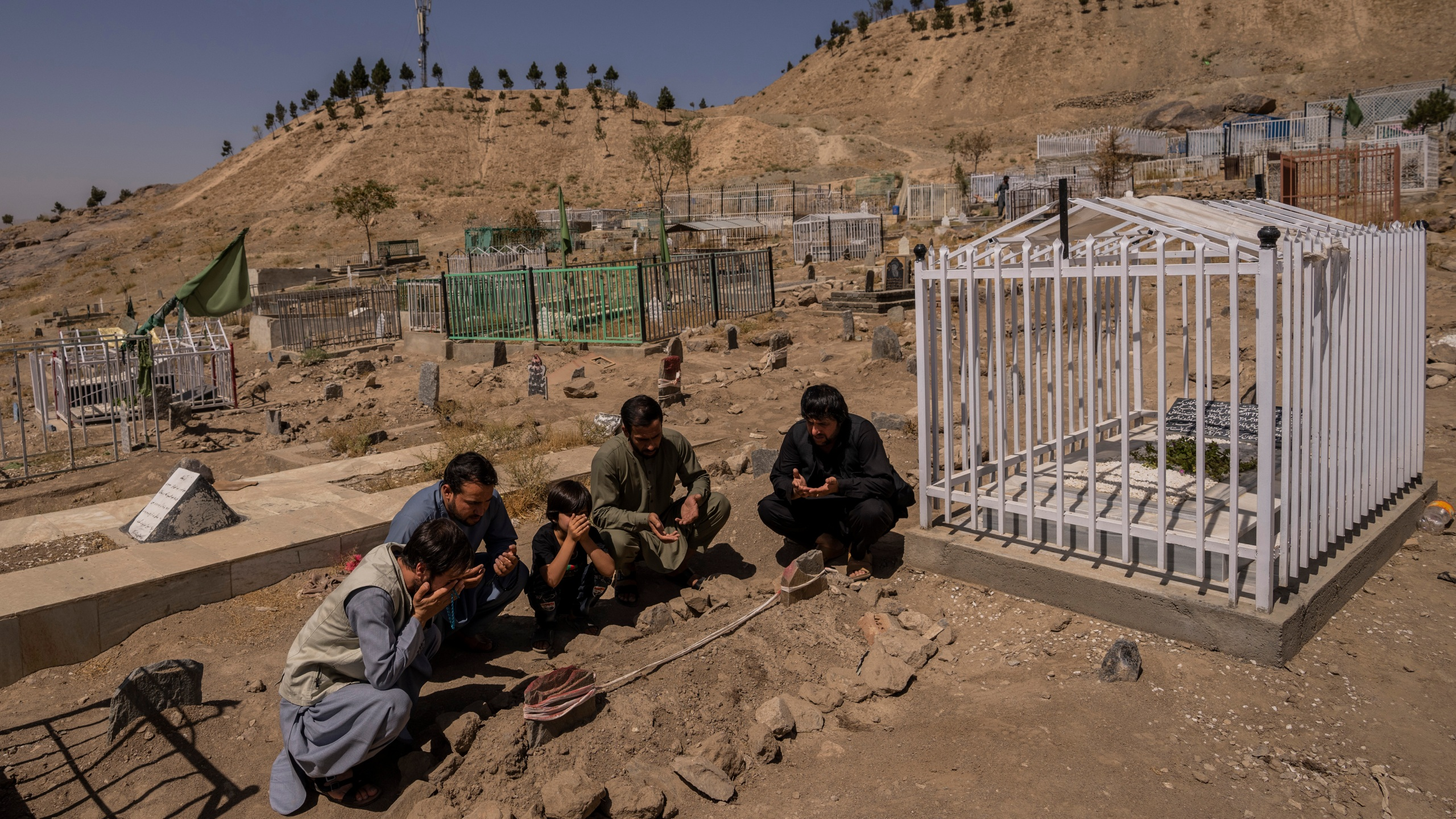 In this Monday, Sept. 13, 2021 file photo, the Ahmadi family pray at the cemetery next to family graves of family members killed by a US drone strike, in Kabul, Afghanistan. (AP Photo/Bernat Armangue, File)
