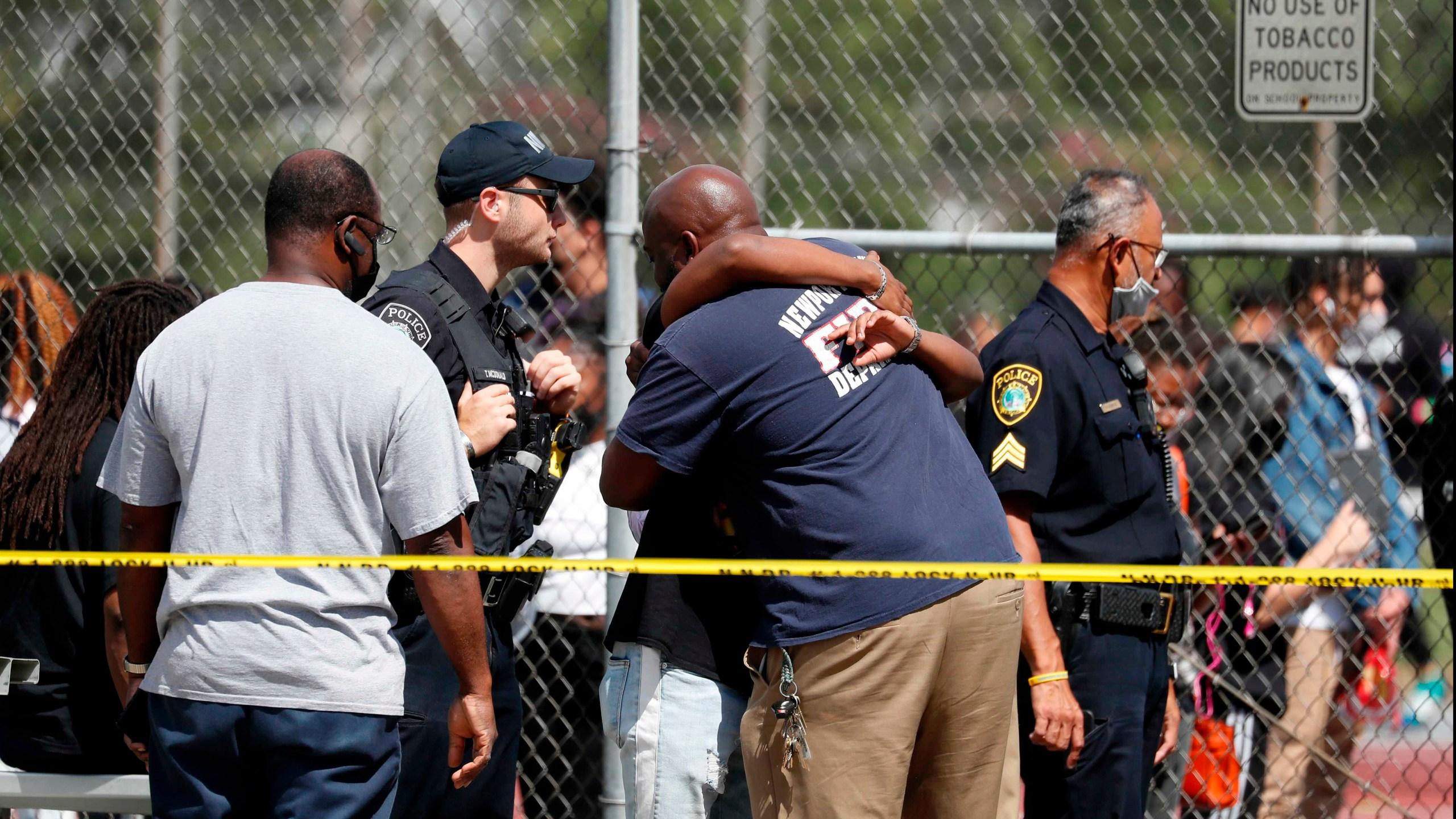 People embrace outside Heritage High School as Newport News Police are on scene responding to a shooting incident Monday, Sept. 20, 2021 in Newport News, Va. (Jonathon Gruenke/The Virginian-Pilot via AP)
