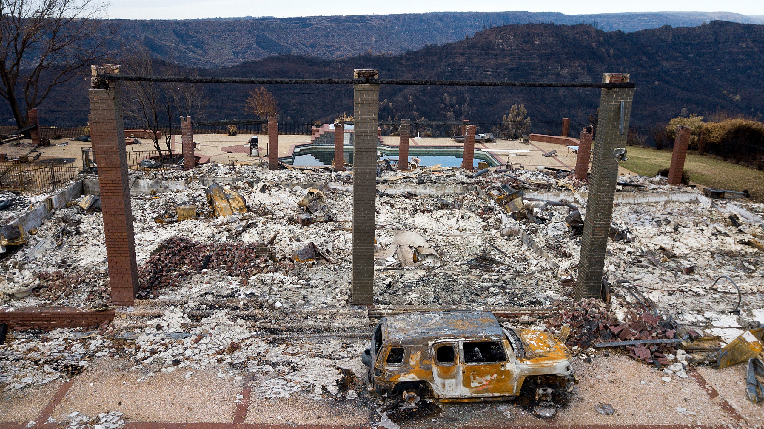 In this Dec. 3, 2018, file photo, a vehicle rests in front of a home leveled by the Camp Fire in Paradise, Calif. (AP Photo/Noah Berger, File)
