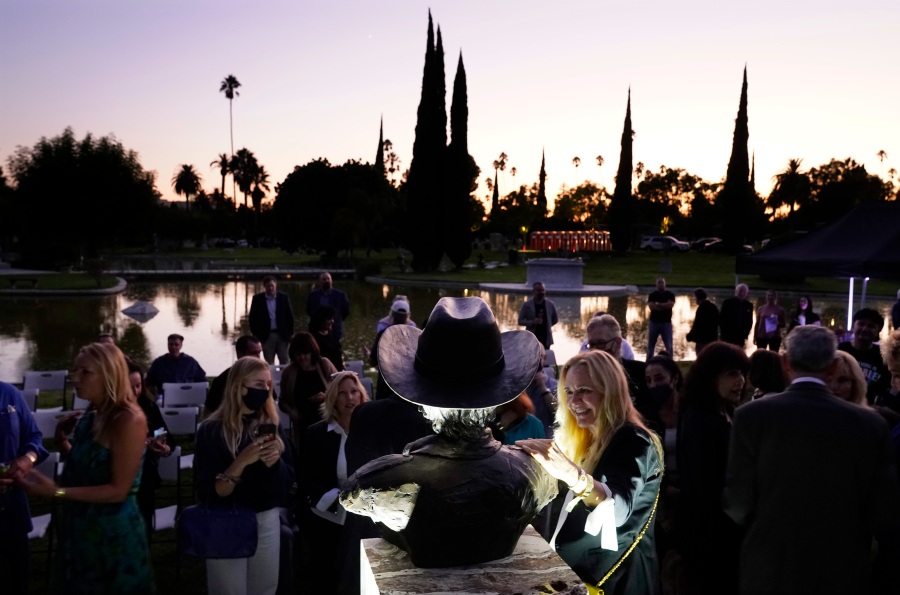 Guests gather around a newly unveiled memorial sculpture of the late actor Burt Reynolds following a ceremony at Hollywood Forever Cemetery on Sept. 20, 2021. (AP Photo/Chris Pizzello)