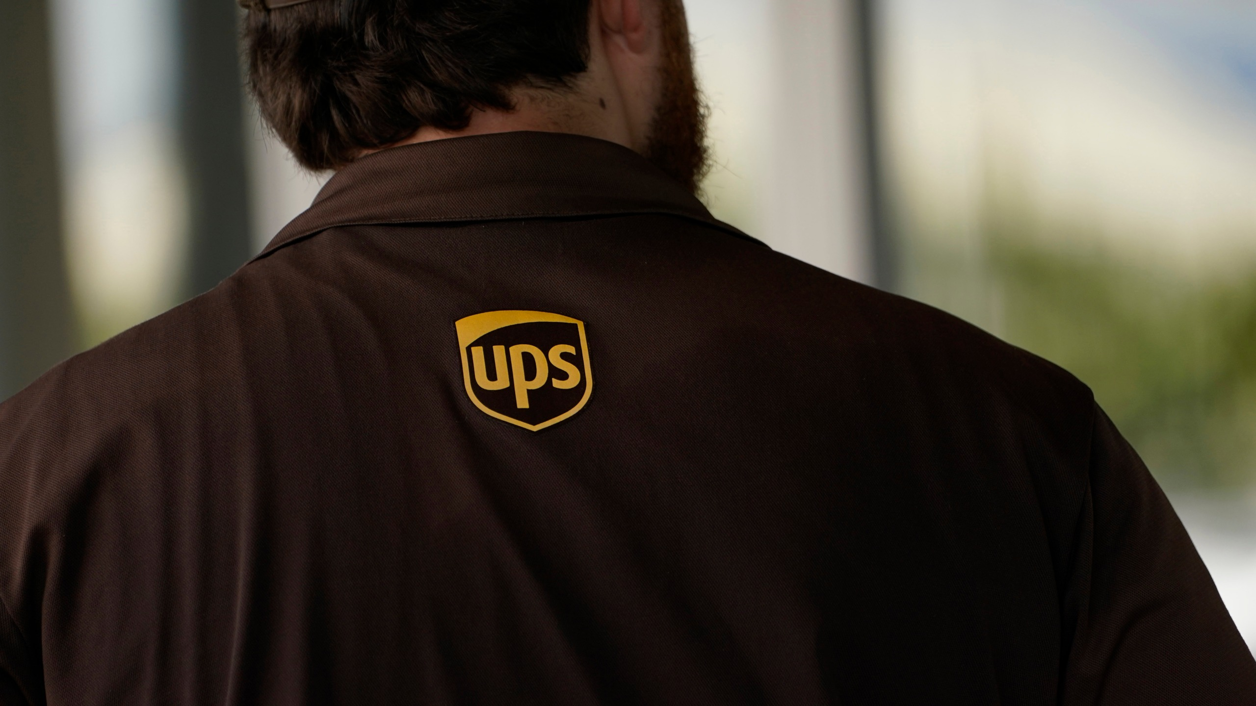 A UPS logo is on the shirt of a driver as he enters a United Parcel Service store with packages in Jackson, Miss., Monday, July 26, 2021. Amazon, Chobani, UPS and more than 30 other companies have vowed to hire and train refugees fleeing Afghanistan for the U.S. The companies said Tuesday, Sept. 21, that they want to help the tens of thousands of Afghan refugees coming to America to integrate into the economy. (AP Photo/Rogelio V. Solis, File)