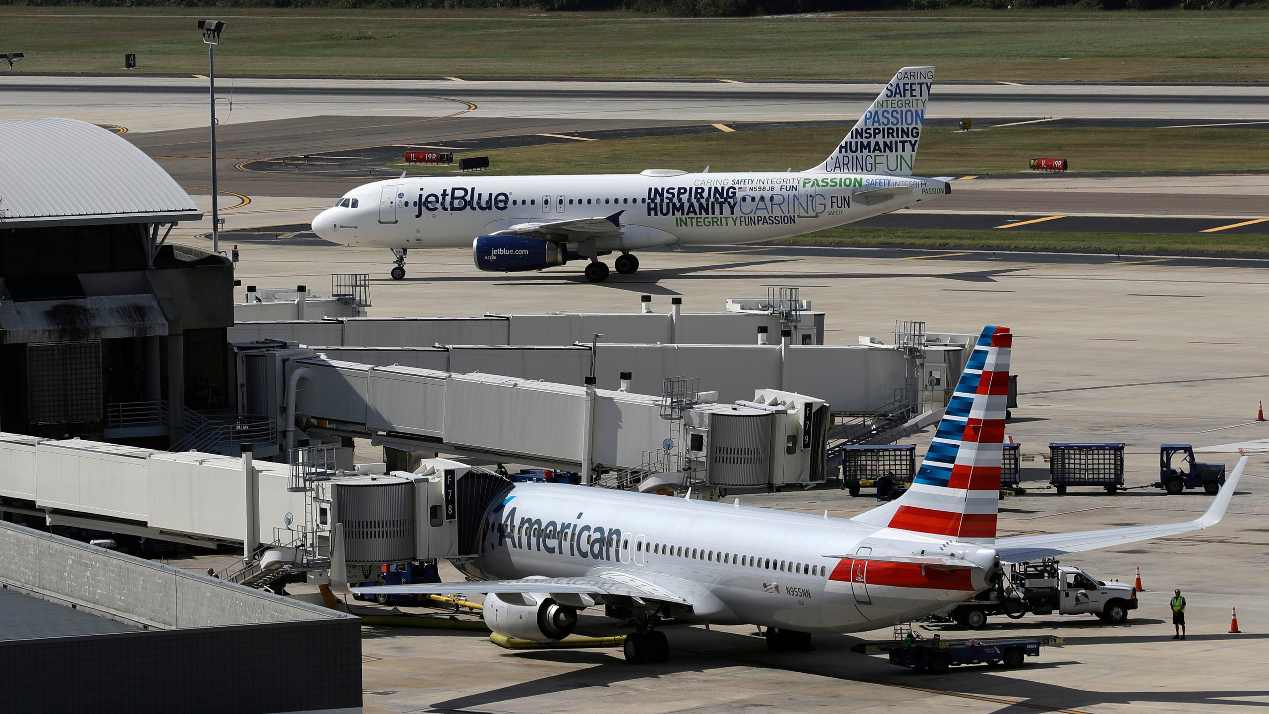 A JetBlue Airbus A320 taxis to a gate Wednesday, Oct. 26, 2016, after landing as an American Airlines jet is seen parked at its gate at Tampa International Airport in Tampa, Fla. (AP Photo/Chris O'Meara, File)
