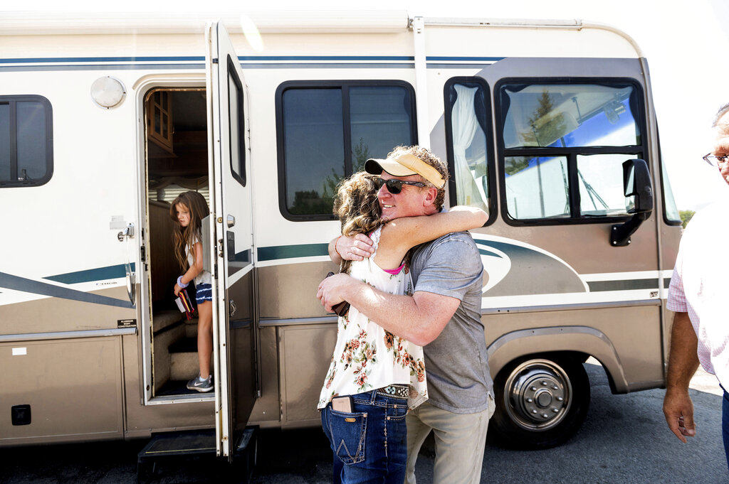 Woody Faircloth hugs Sheri Roen as her family donates their motorhome to EmergencyRV.org on Sunday, Sept. 5, 2021, in Sierra County, Calif. (AP Photo/Noah Berger)