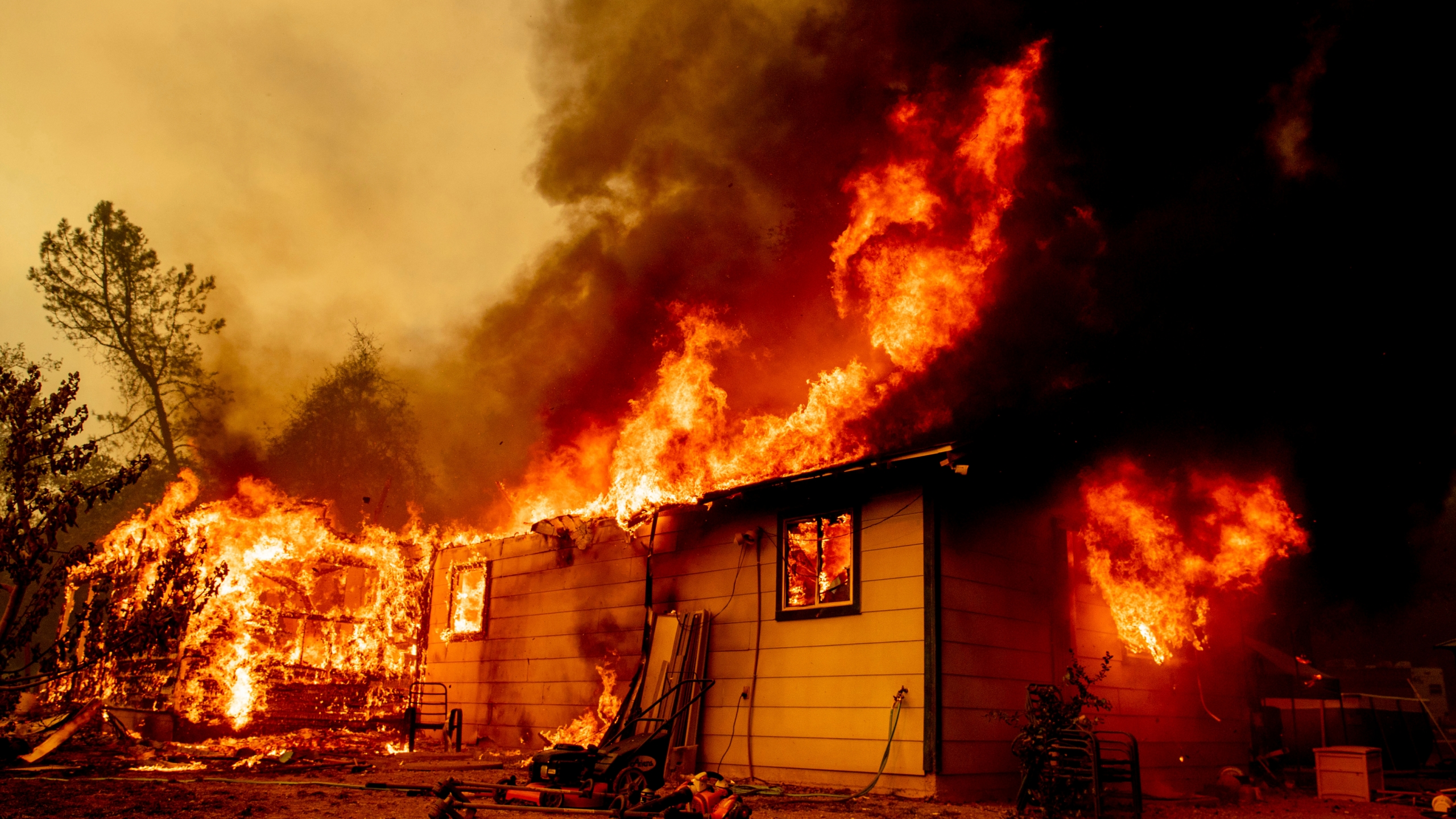 Flames consume a house near Old Oregon Trail as the Fawn Fire burns about 10 miles north of Redding in Shasta County, Calif., on Sep. 23, 2021. (Ethan Swope/Associated Press)