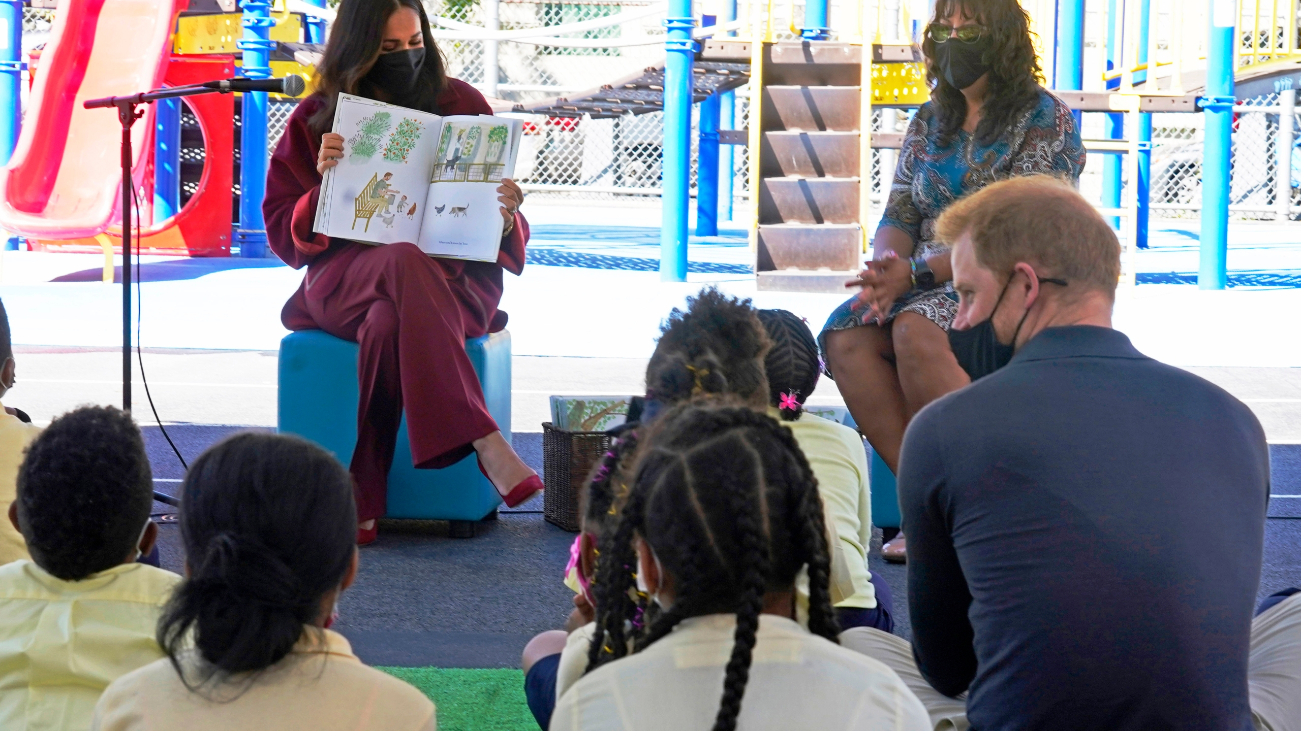 """Meghan, the Duchess of Sussex, reads from her book """"The Bench,"""" as Prince Harry, the Duke of Sussex, foreground right, and second grade students listen, during their visit to P.S. 123, the Mahalia Jackson School, in New York's Harlem neighborhood on Sept. 24, 2021. (AP Photo/Richard Drew)"""