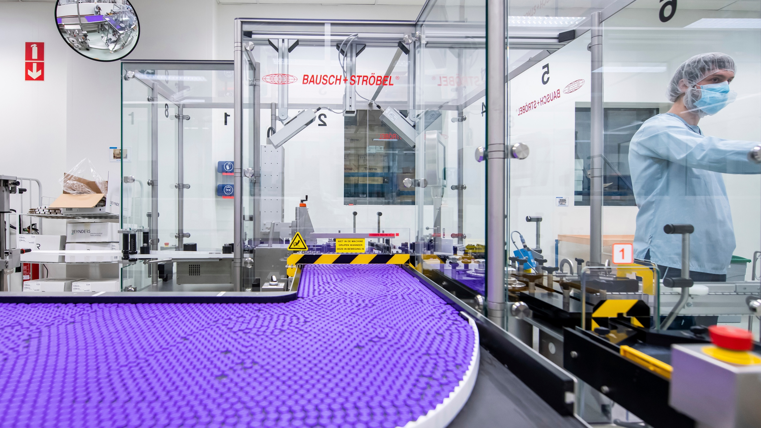 In this March 2021 photo provided by Pfizer, a technician works on a line for packaging preparation for the Pfizer-BioNTech COVID-19 vaccine at the company's facility in Puurs, Belgium. (Pfizer via AP)