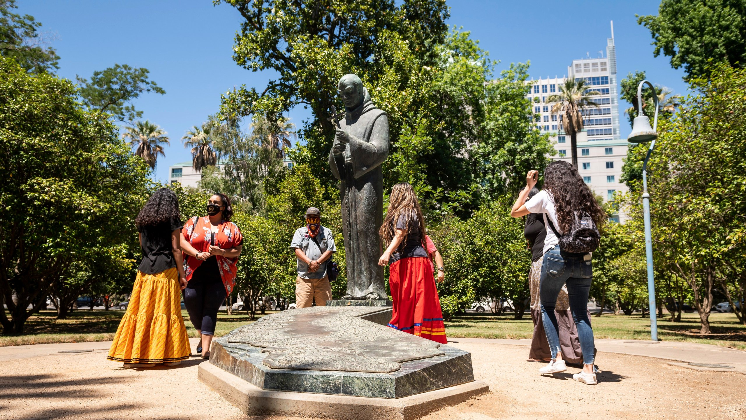 In this June 16, 2020, photo, people gather near the Father Junipero Serra statue on the Capitol Park grounds in Sacramento, Calif. (Xavier Mascarenas/The Sacramento Bee via Associated Press)