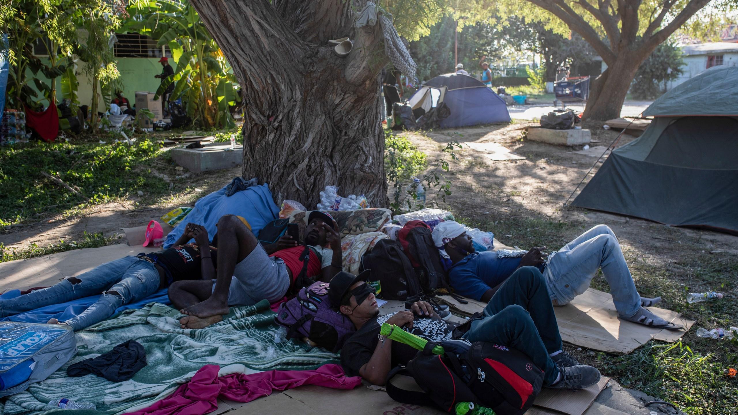 Migrants rest under the shade of a tree in Ciudad Acuna, Mexico, Friday, Sept. 24, 2021, across the Rio Grande from Del Rio, Texas. (AP Photo/Felix Marquez)