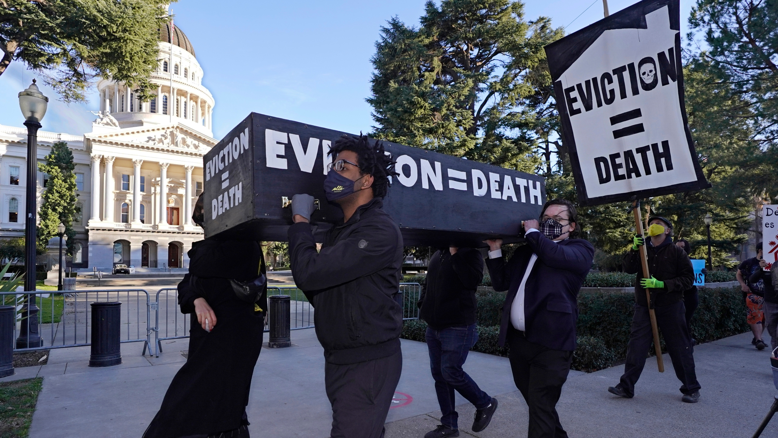 Demonstrators call for passage of rent forgiveness and stronger eviction protections legislation as they carry a mock casket past the Capitol in Sacramento on Jan. 25, 2021. (Rich Pedroncelli / Associated Press)