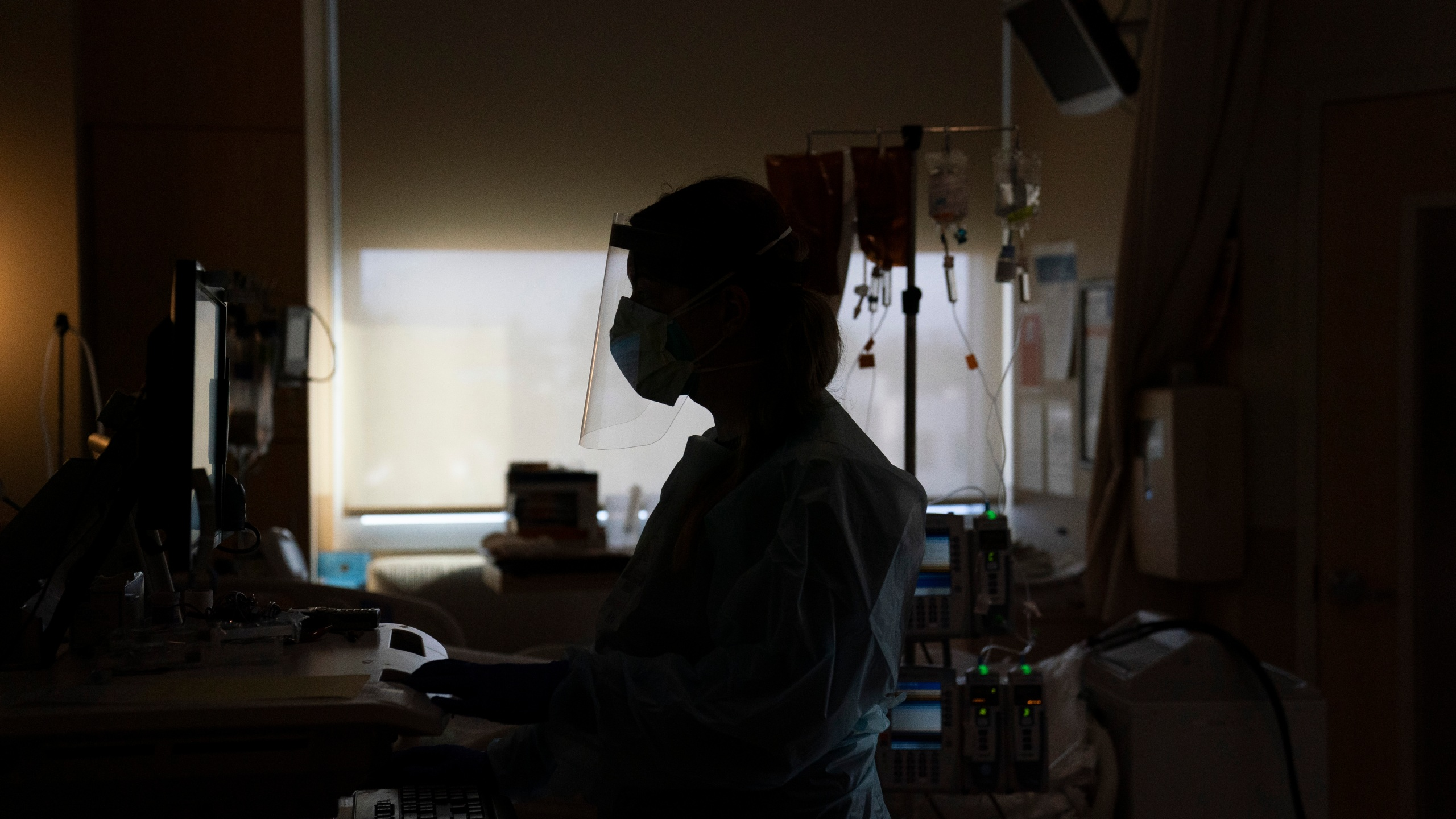In this Nov. 19, 2020, file photo, a nurse works on a computer while assisting a COVID-19 patient at a hospital in Los Angeles. Across the country, doctors and nurses on the front lines of the coronavirus pandemic are dealing with hostility, threats and violence from patients angry over safety rules designed to keep the virus from spreading. (AP Photo/Jae C. Hong, File)