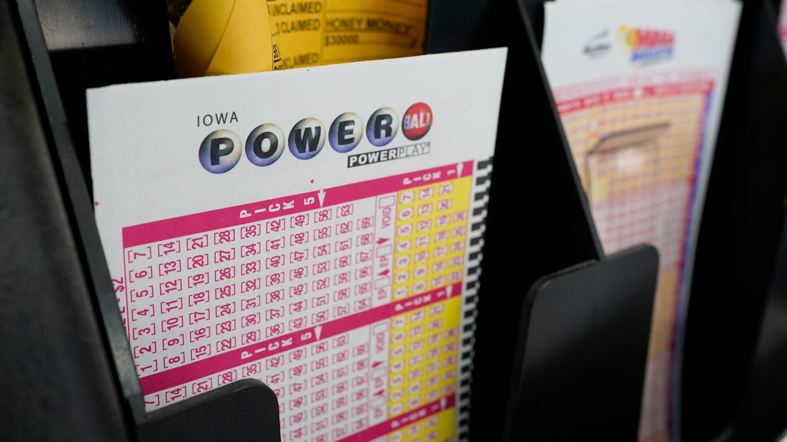 In this Jan. 12, 2021 file photo, blank forms for the Powerball lottery sit in a bin at a local grocery store, in Des Moines, Iowa. (AP Photo/Charlie Neibergall)
