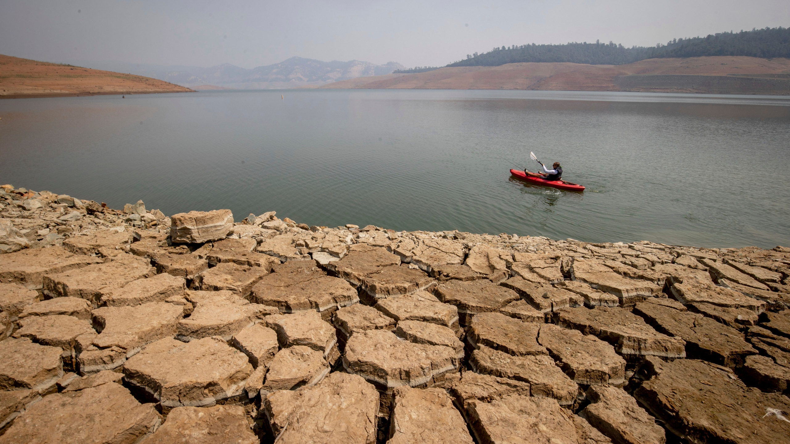A kayaker fishes in Lake Oroville as water levels remain low due to continuing drought conditions on Aug. 22, 2021. (Ethan Swope / Associated Press)