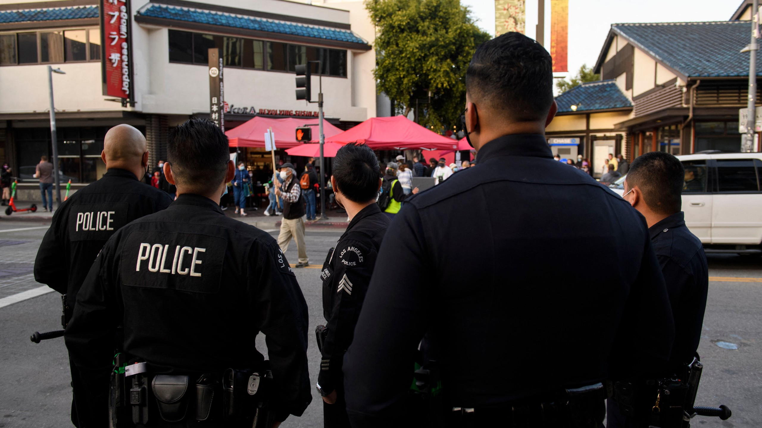 Los Angeles Police Department (LAPD) officers watch as a memorial procession for nursing home residents who died due to Covid-19 proceeds on March 20, 2021, in the Little Tokyo neighborhood of Los Angeles. (PATRICK T. FALLON/AFP via Getty Images)