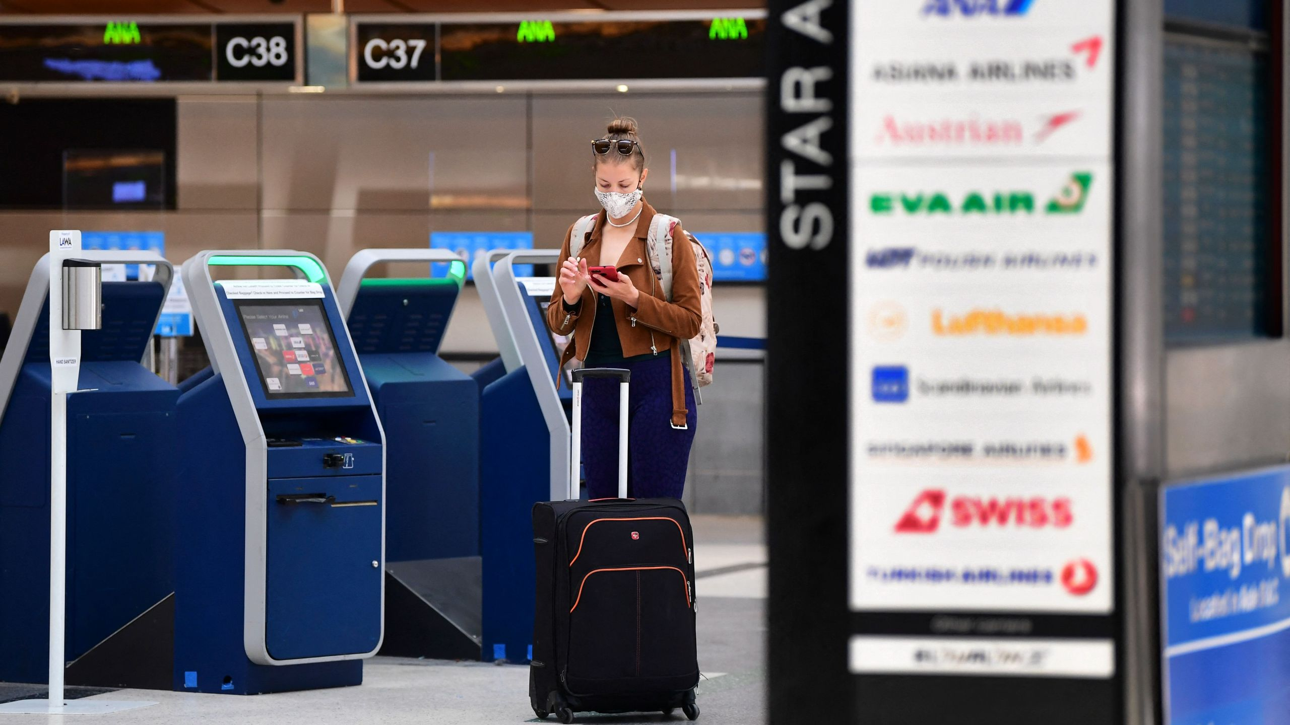 A woman stands by the self check-in kiosks on the departures level of Los Angeles International Airport (LAX) on May 27, 2021 in Los Angeles. (FREDERIC J. BROWN/AFP via Getty Images)