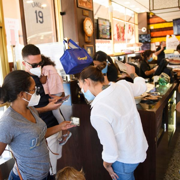 An employee checks a digital vaccine card for proof of COVID-19 vaccination at Langer's Deli in Los Angeles on Aug. 7, 2021. (PATRICK T. FALLON/AFP via Getty Images)