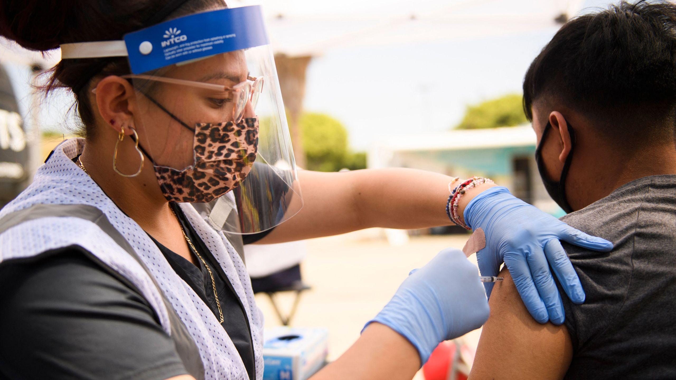A 17-year-old receives a first dose of the Pfizer COVID-19 vaccine at a mobile vaccination clinic during a back to school event at the Weingart East Los Angeles YMCA in Los Angeles on Aug. 7, 2021. (PATRICK T. FALLON/AFP via Getty Images)