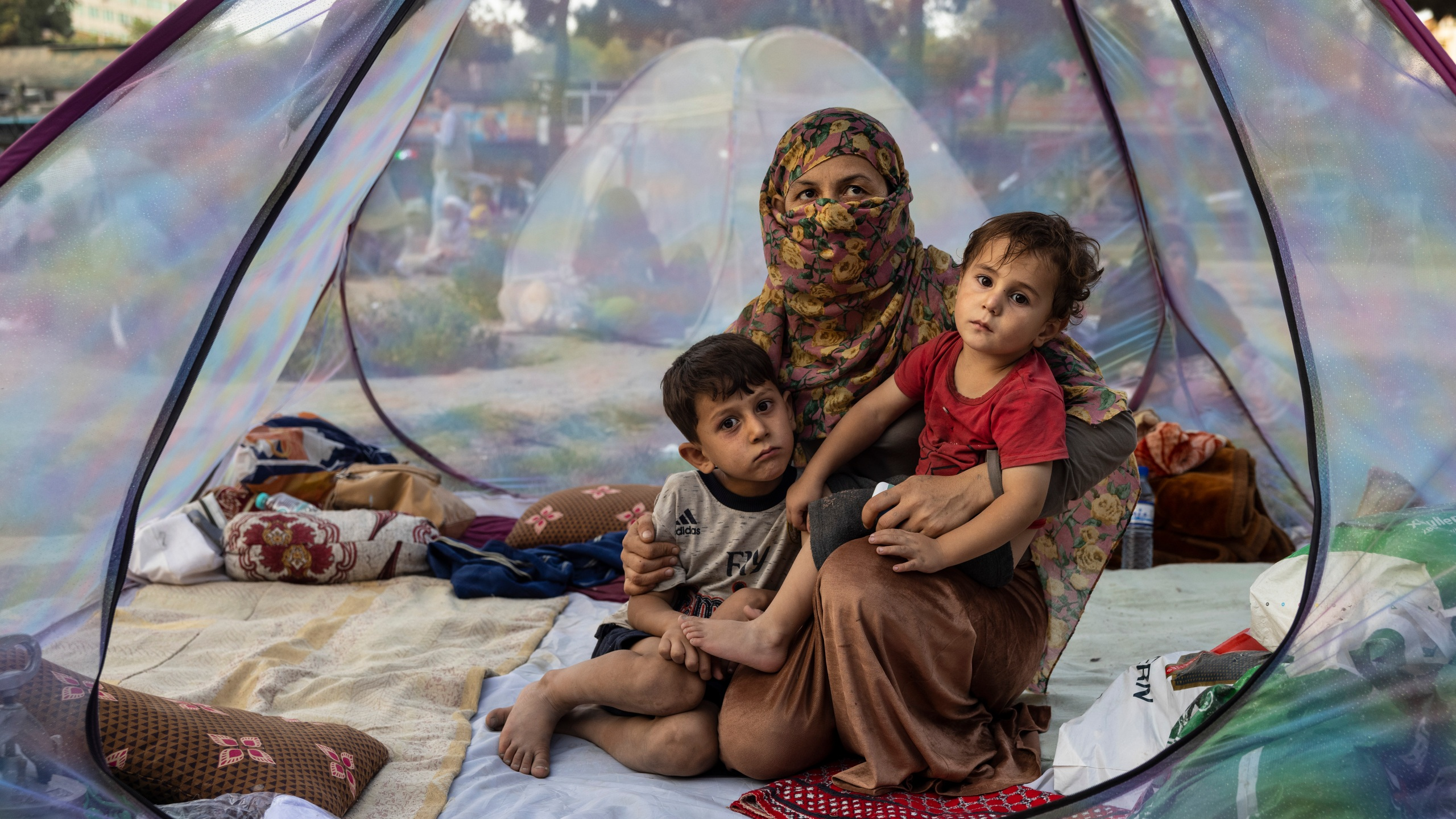 Farzia, 28, who lost her husband in Baghlan one week ago to fighting by the Taliban sits with her children, Subhan, 5, and Ismael ,2, in a tent at a makeshift IDP camp in Share-e-Naw park to various mosques and schools on August 12, 2021 in Kabul, Afghanistan. (Paula Bronstein/Getty Images)