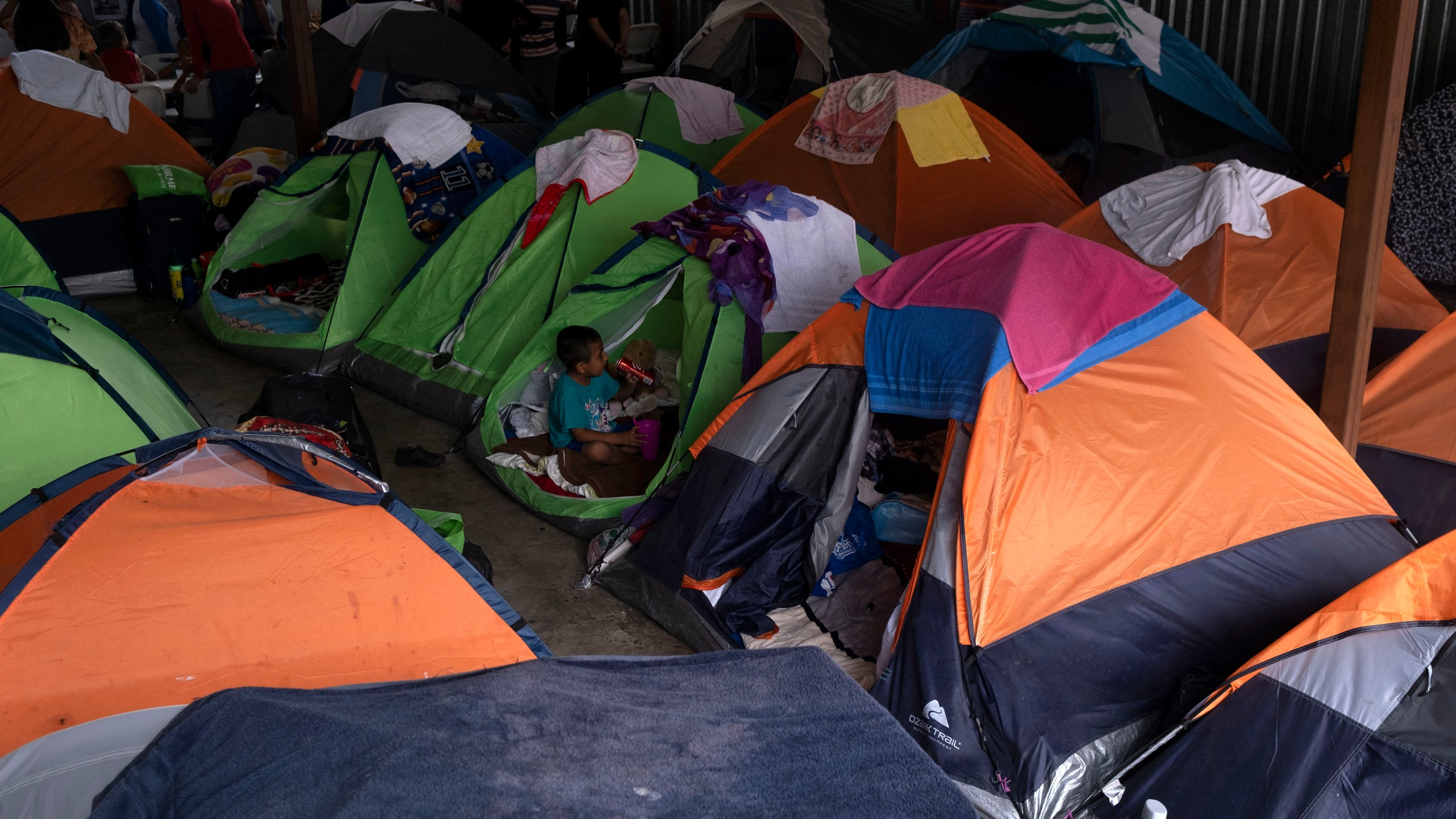 Asylum seekers and migrants are seen at a shelter in Tijuana, Baja Caifornia state, on Aug. 20, 2021. (Guillermo Arias / AFP / Getty Images)