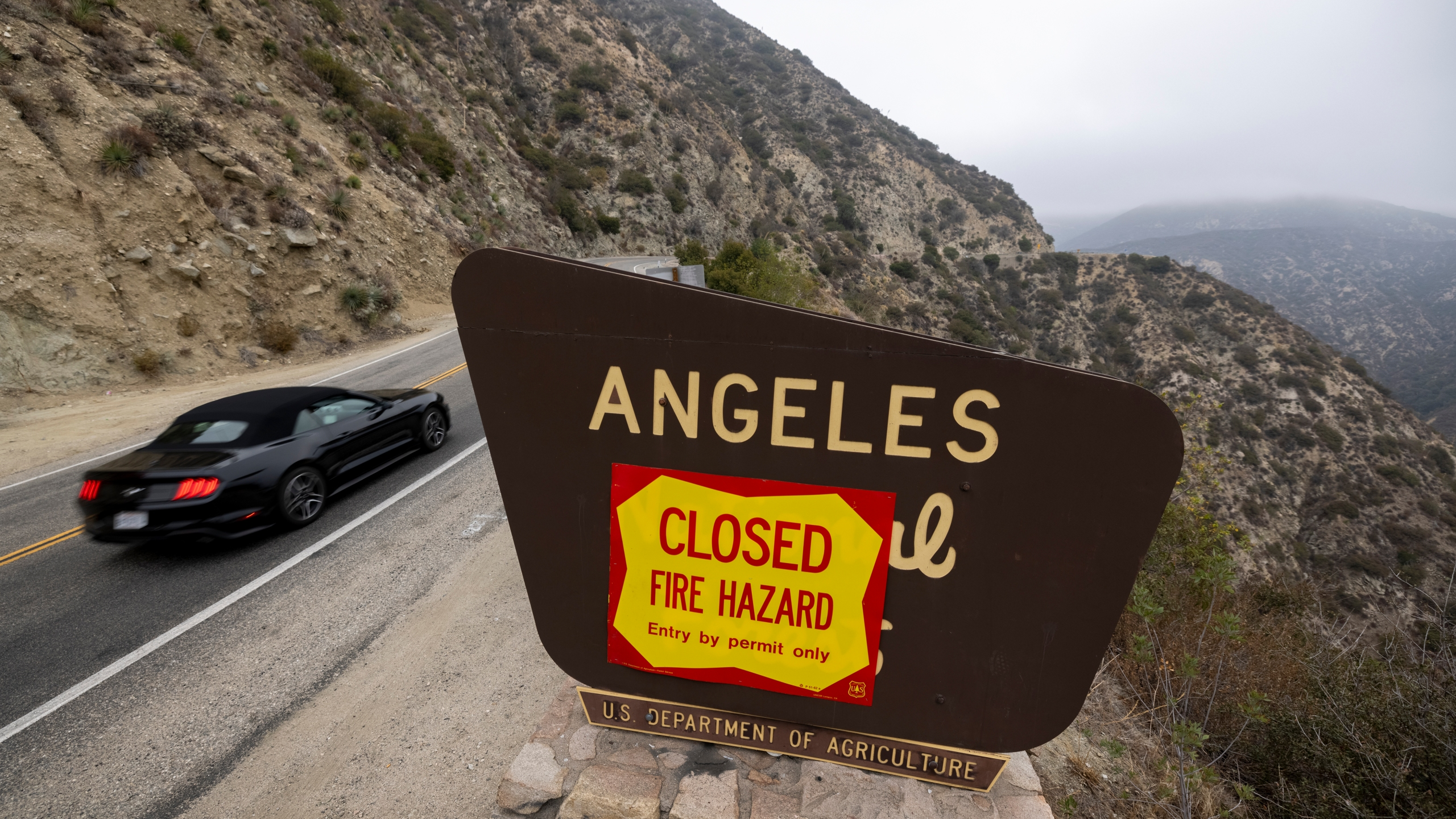 A motorcyclist passes forest closure signage along the Angeles Crest Highway in the Angeles National Forest on Sept. 2, 2021, near La Canada Flintridge, California. (David McNew/Getty Images)
