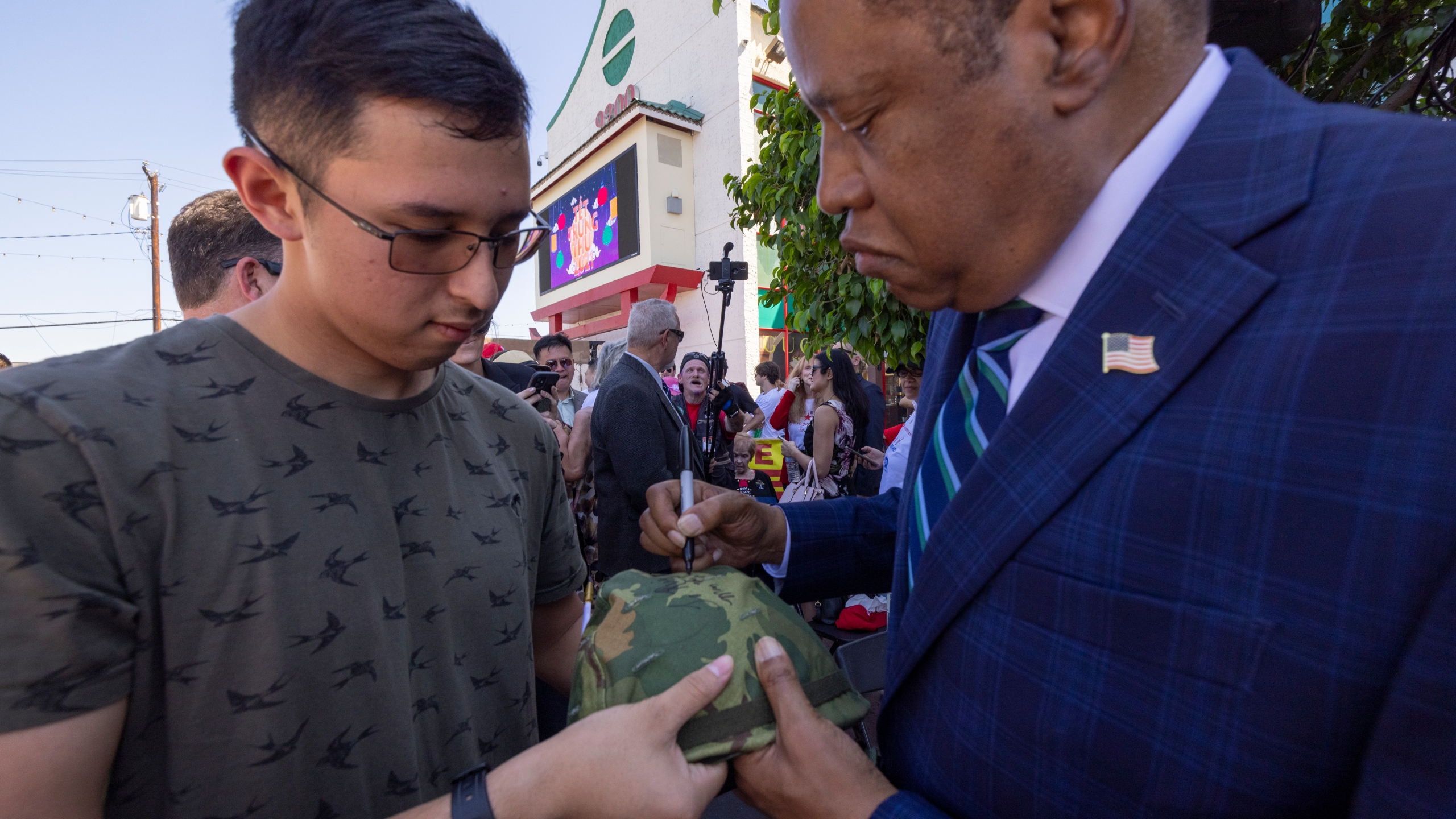 """Republican recall candidate Larry Elder signs the helmet of U.S. Navy ETSN Daniel Luiz at the """"Asian Rally for Yes on Recall"""" at the Asian Garden Mall on Sept. 4, 2021, in Westminster. (David McNew/Getty Images)"""