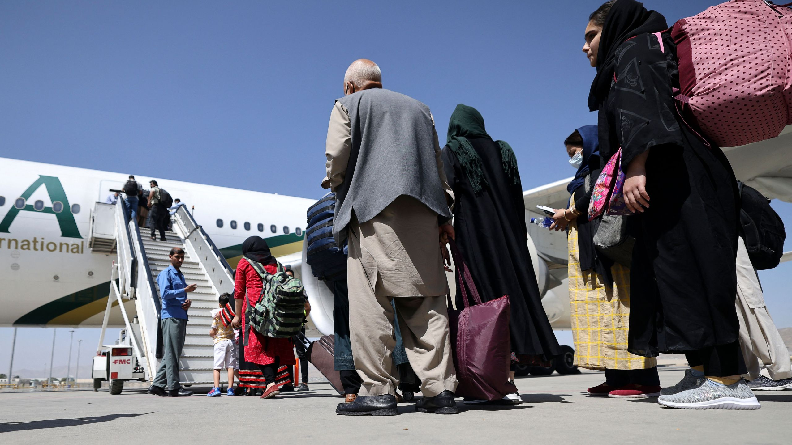 Passengers stand in a queue to board a Pakistan International Airlines plane, the first international commercial flight to land since the Taliban retook power in Afghanistan, at the airport in Kabul on Sept. 13, 2021. (Karim Sahib / AFP / Getty Images)