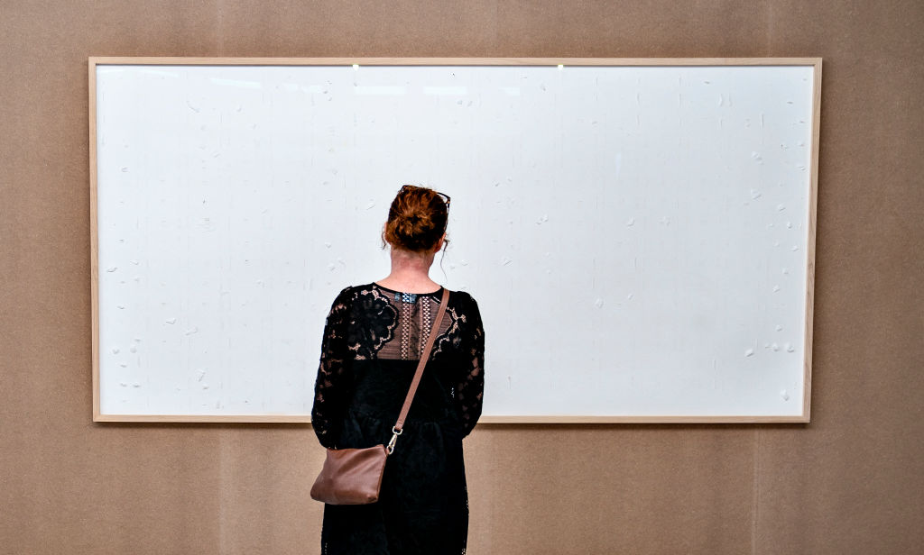 A woman stands in front of an empty frame hung up at the Kunsten Museum in Aalborg, Denmark, on September 28 2021. (HENNING BAGGER/Ritzau Scanpix/AFP via Getty Images)