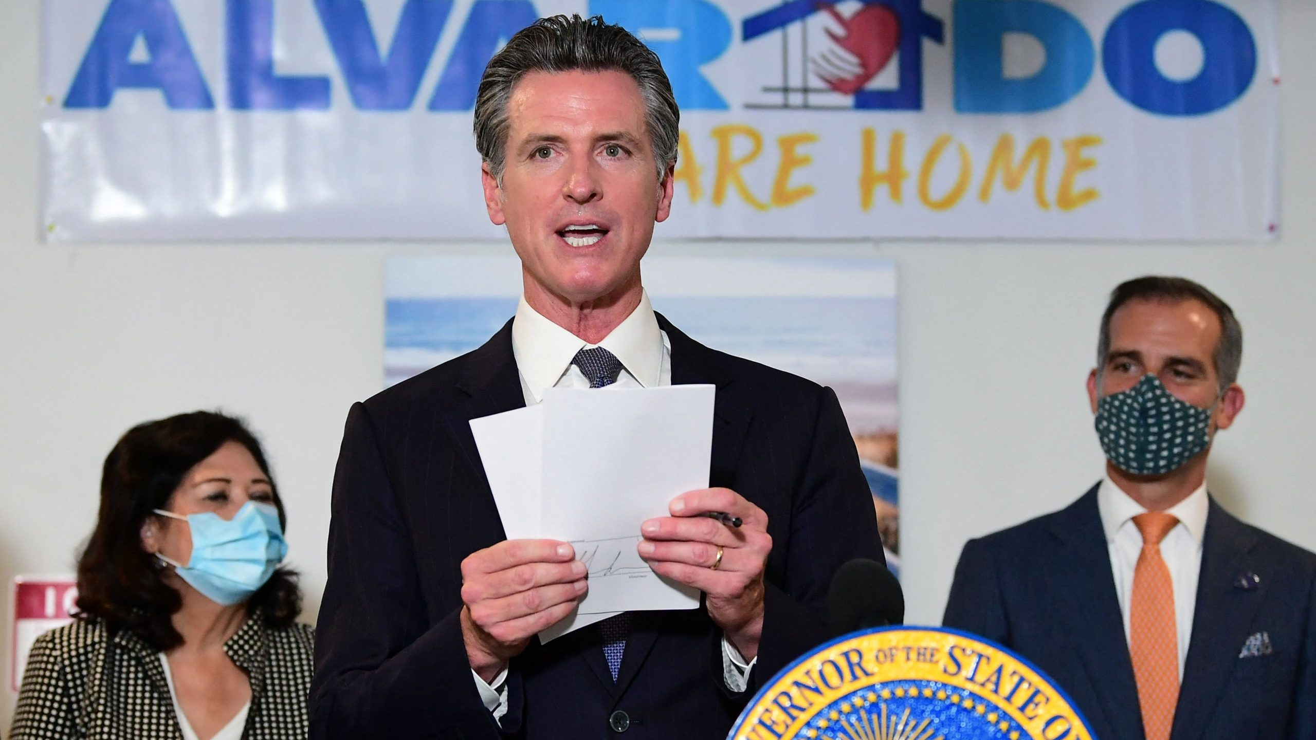 California Gov. Gavin Newsom, flanked by Los Angeles Mayor Eric Garcetti, at right, displays the seven bills signed as he joins city leaders in Los Angeles in celebration of legislation to support the state's expansion of mental health services and behavioral health housing as part of California's package to address the homeless crisis on Sept. 29, 2021. (Frederic J. Brown / AFP / Getty Images)