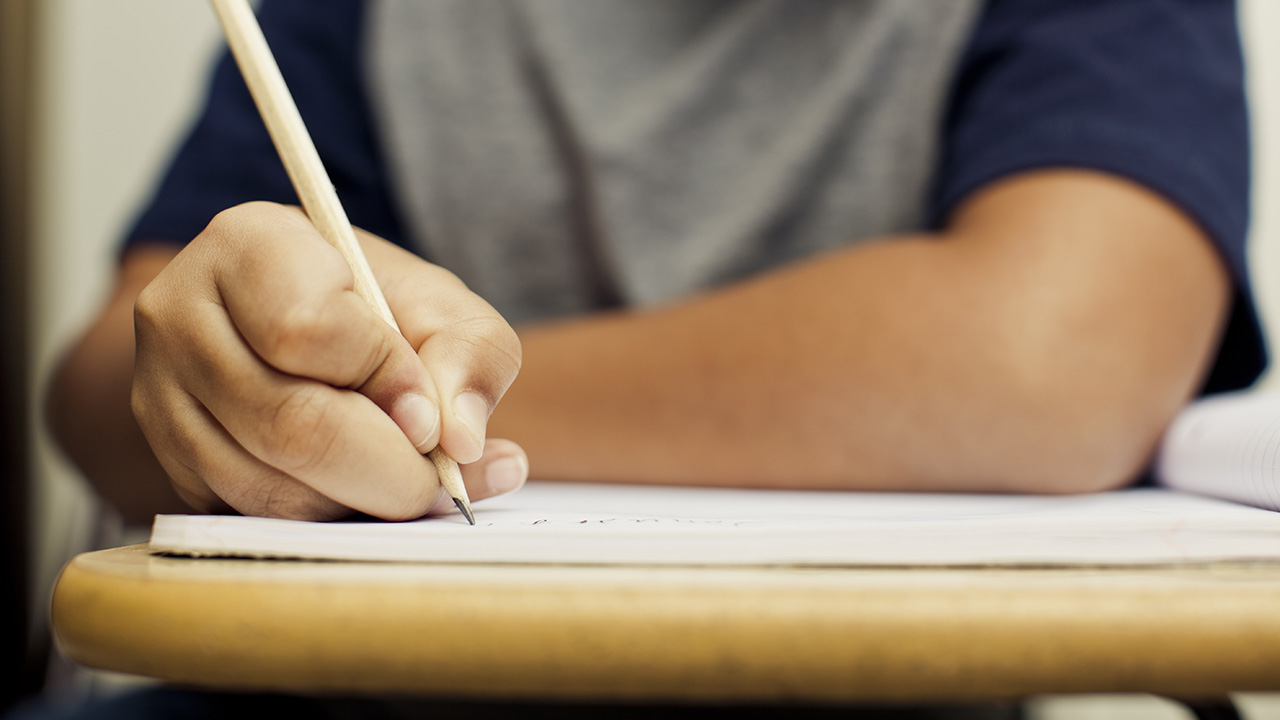 A student writes at a desk in this undated file photo. (Getty Images)
