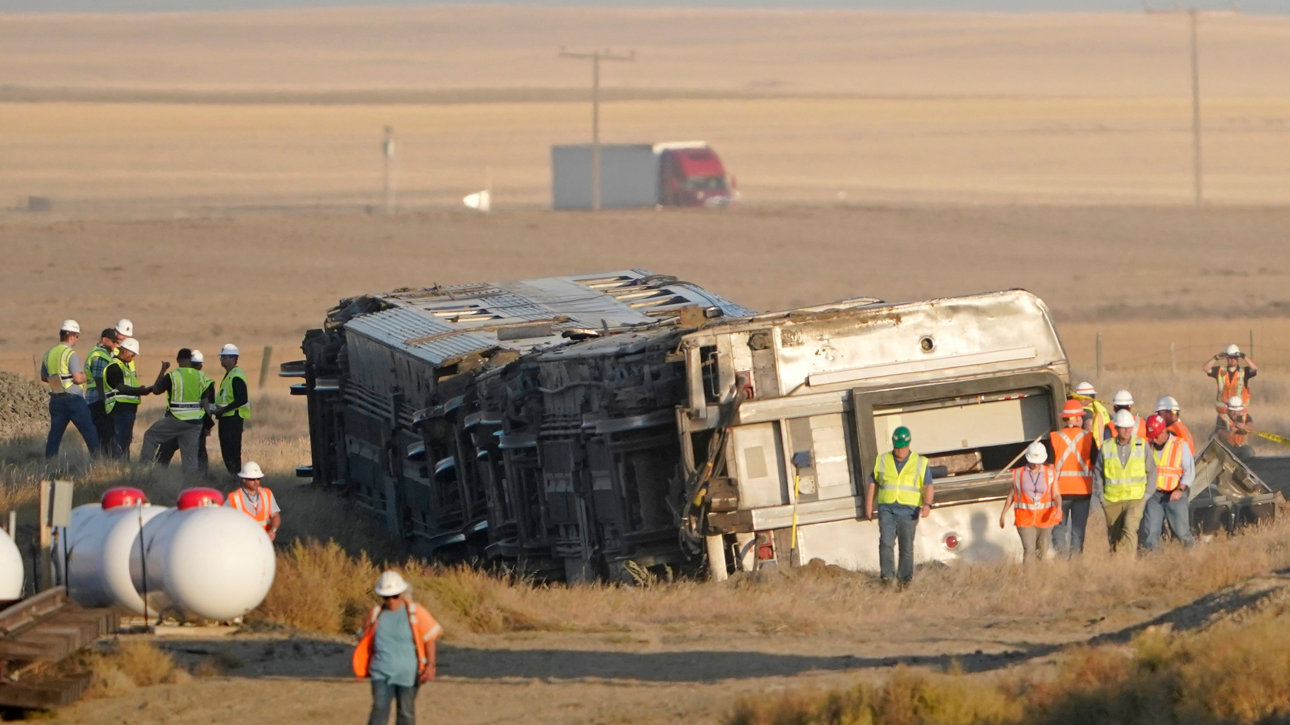 Workers stand Sunday, Sept. 26, 2021, near toppled cars from an Amtrak train that derailed Saturday, just west of Joplin, Mont. The westbound Empire Builder was en route to Seattle from Chicago with two locomotives and 10 cars. (AP Photo/Ted S. Warren)