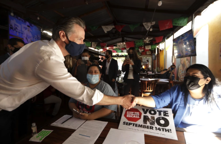 Gov. Gavin Newsom greets volunteers working phone banks in support of voting against the recall on Aug. 14 at Hecho en Mexico restaurant in East Los Angeles.(Genaro Molina / Los Angeles Times)