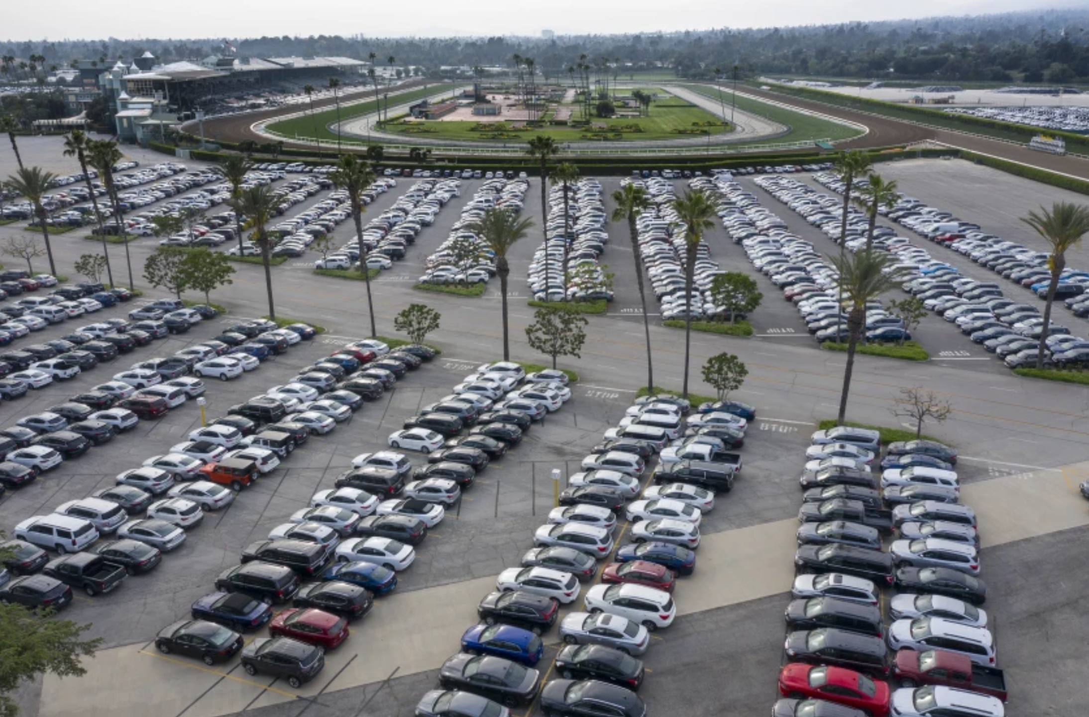 When the pandemic first hit, demand for rental cars plummeted, forcing rental companies to park thousands of cars in lots such as the Santa Anita racetrack parking lot, shown in April 2020. Many of those cars were later sold.(Robert Gauthier / Los Angeles Times)