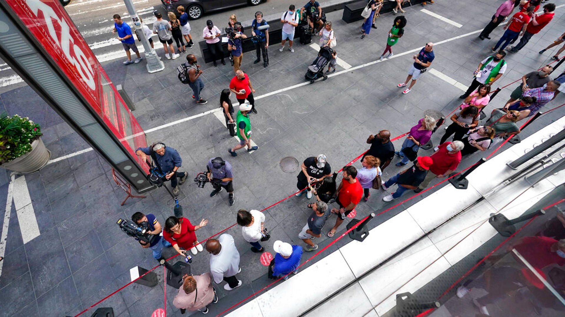 A television crew interviews the first people in line to buy discounted Broadway show tickets at TKTS, Tuesday, Sept. 14, 2021, in New York's Times Square. (AP Photo/Mary Altaffer)