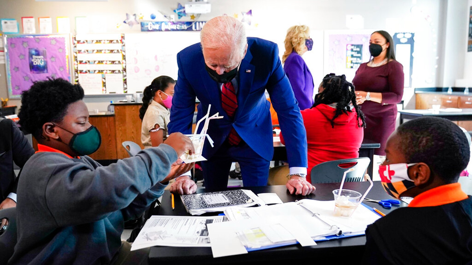 In this Sept. 10, 2021, file photo President Joe Biden talks to students at Brookland Middle School in Washington, as first lady Jill Biden talks with Brookland Middle School science teacher Michelle Taylor, right rear. (AP Photo/Manuel Balce Ceneta, File)