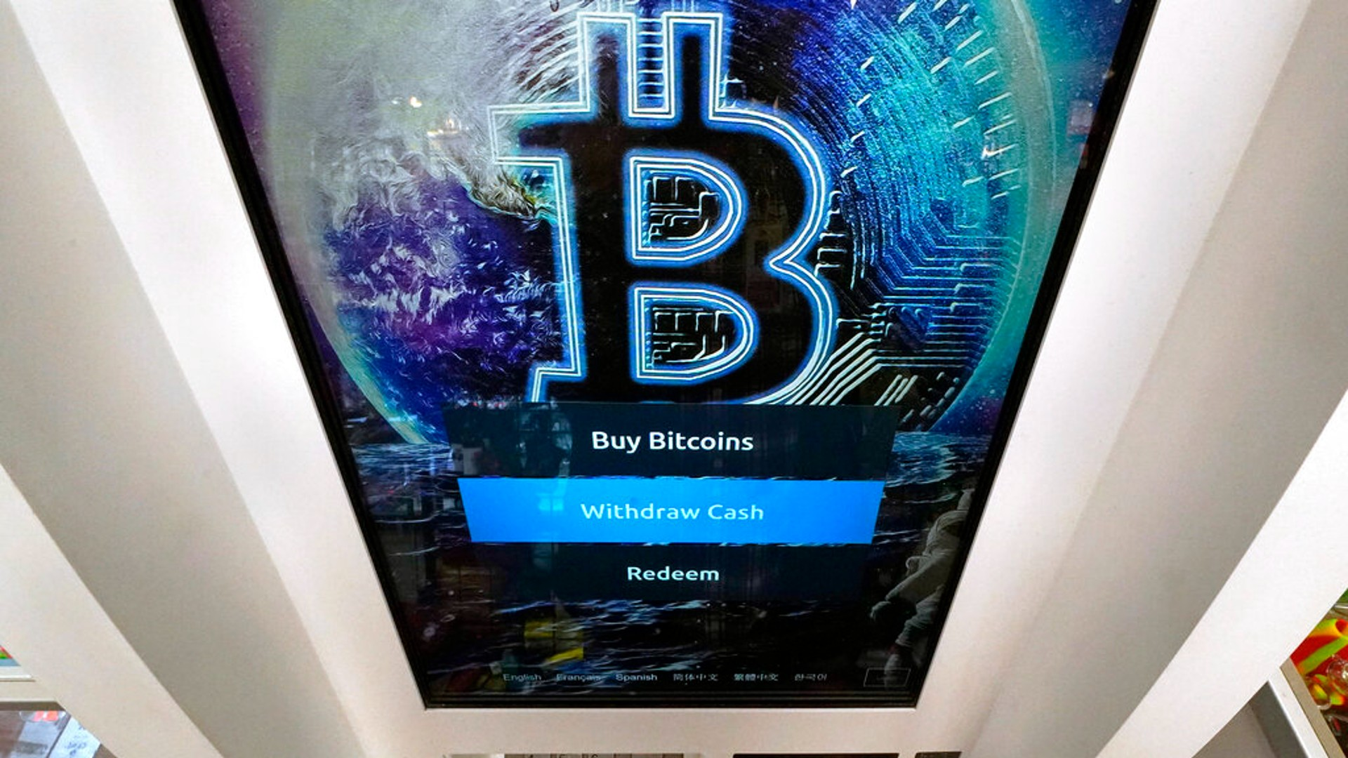 In this Feb. 9, 2021, file photo, the Bitcoin logo appears on the display screen of a cryptocurrency ATM at the Smoker's Choice store in Salem, N.H. (AP Photo/Charles Krupa, File)