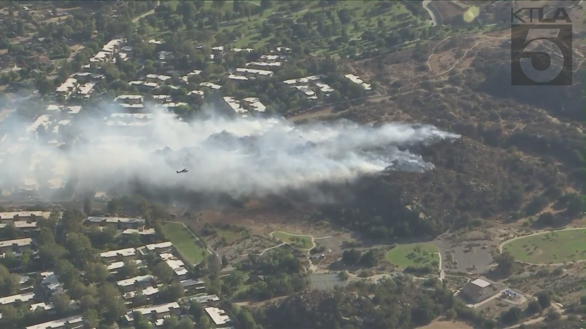 Smoke rises from a hillside in Chatsworth while crews battle a fire on Sept. 22, 2021. (KTLA)