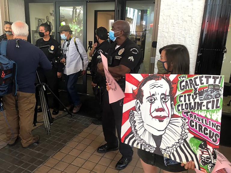 Carla Orendorff, holding a sign targeting Garcetti, protests outside a new department focused on civil rights on Sept. 13, 2021. (Dakota Smith / Los Angeles Times)