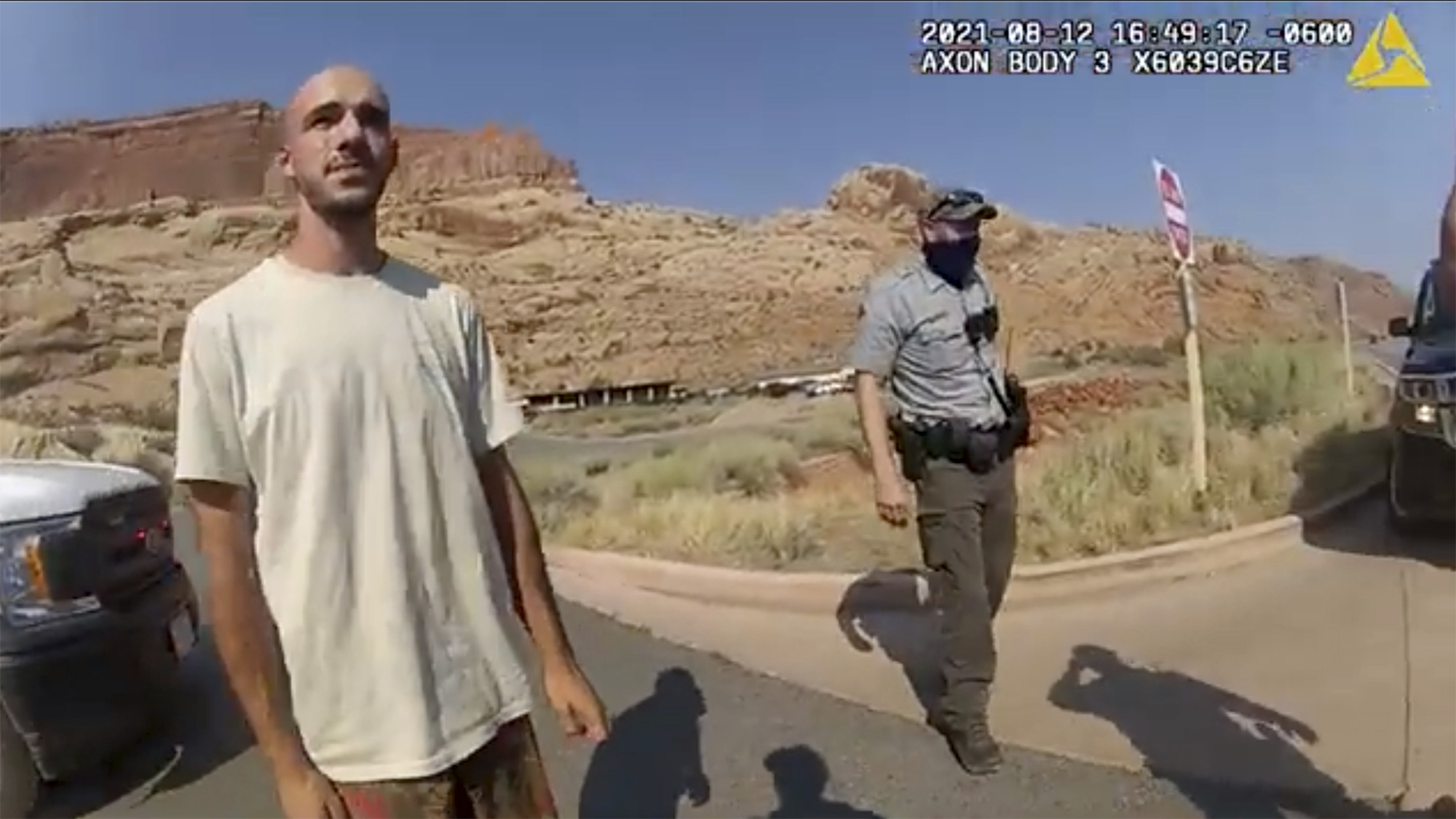 """This police camera video provided by the Moab Police Department shows Brian Laundrie talking to a police officer after police pulled over the van he was traveling in with his girlfriend, Gabrielle """"Gabby"""" Petito, near the entrance to Arches National Park on Aug. 12, 2021. The couple was pulled over while they were having an emotional fight. (The Moab Police Department via Associated Press)"""