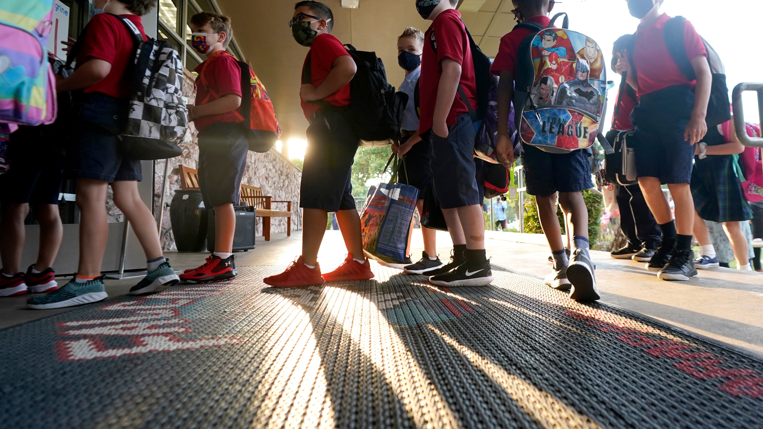 Wearing masks to prevent the spread of COVID-19, elementary school students line up to enter school for the first day of classes in Richardson, Texas, Tuesday, Aug. 17, 2021. (AP Photo/LM Otero)