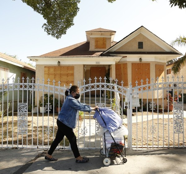 A woman walks past a boarded-up home on East 27th Street in South L.A. in August 2021. (Al Seib / Los Angeles Times)
