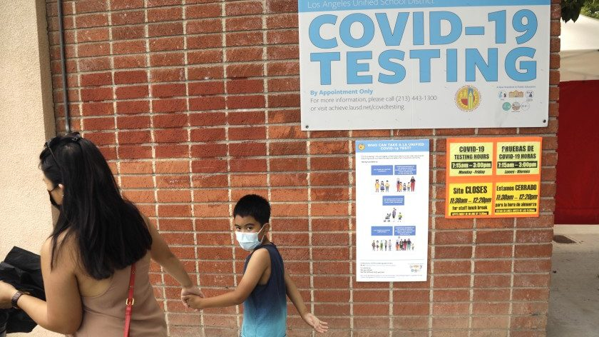 A student and parent walk past a sign advertising COVID-19 testing on an Los Angeles Unified School District campus in this undated photo. (Genaro Molina / Los Angeles Times)