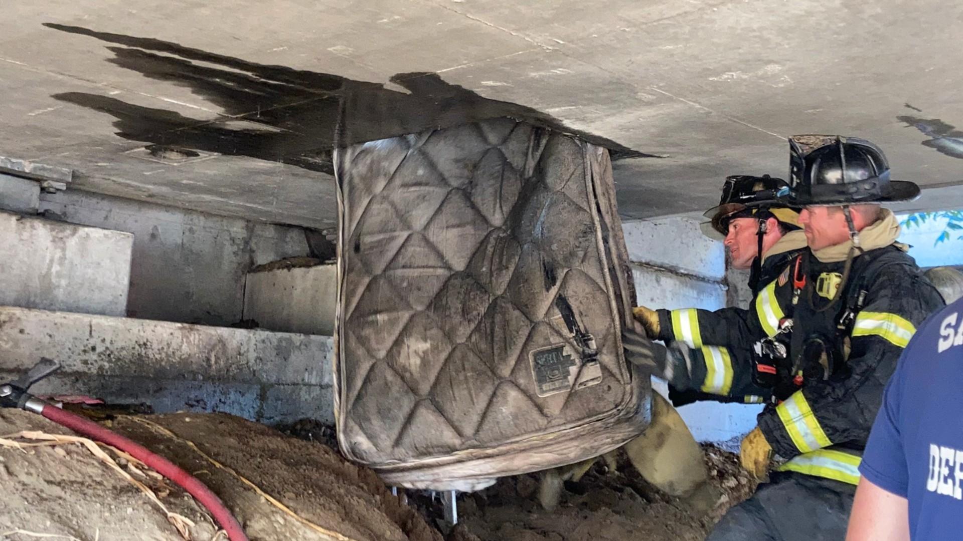 Sacramento firefighters remove a mattress from underneath an overpass on Highway 160. (Sacramento Fire Department)