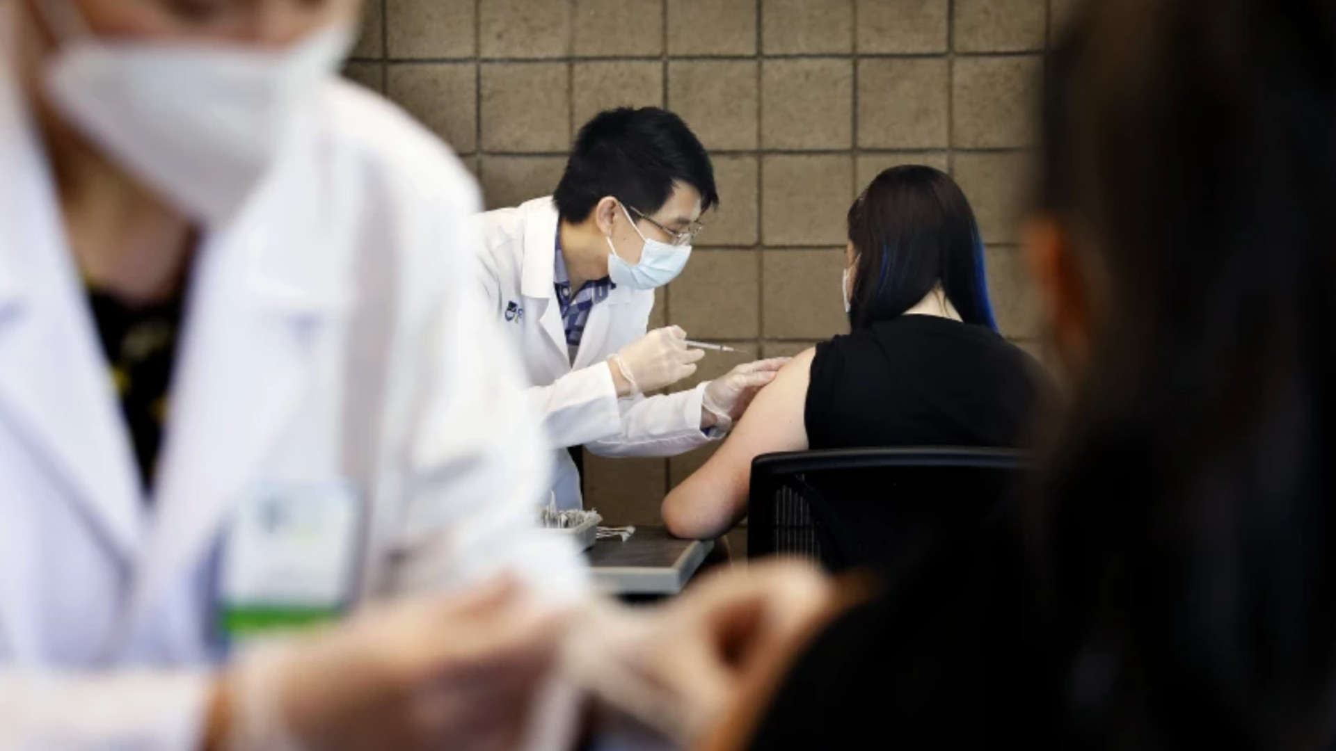 Sarith Mey, center, a pharmacist graduat intern with Rite Aid, administers a shot to CSUDH student Fritzi Bui, during a COVID-19 vaccination clinic hosted by Cal State Dominguez Hills in Carson.(Christina House/Los Angeles Times)