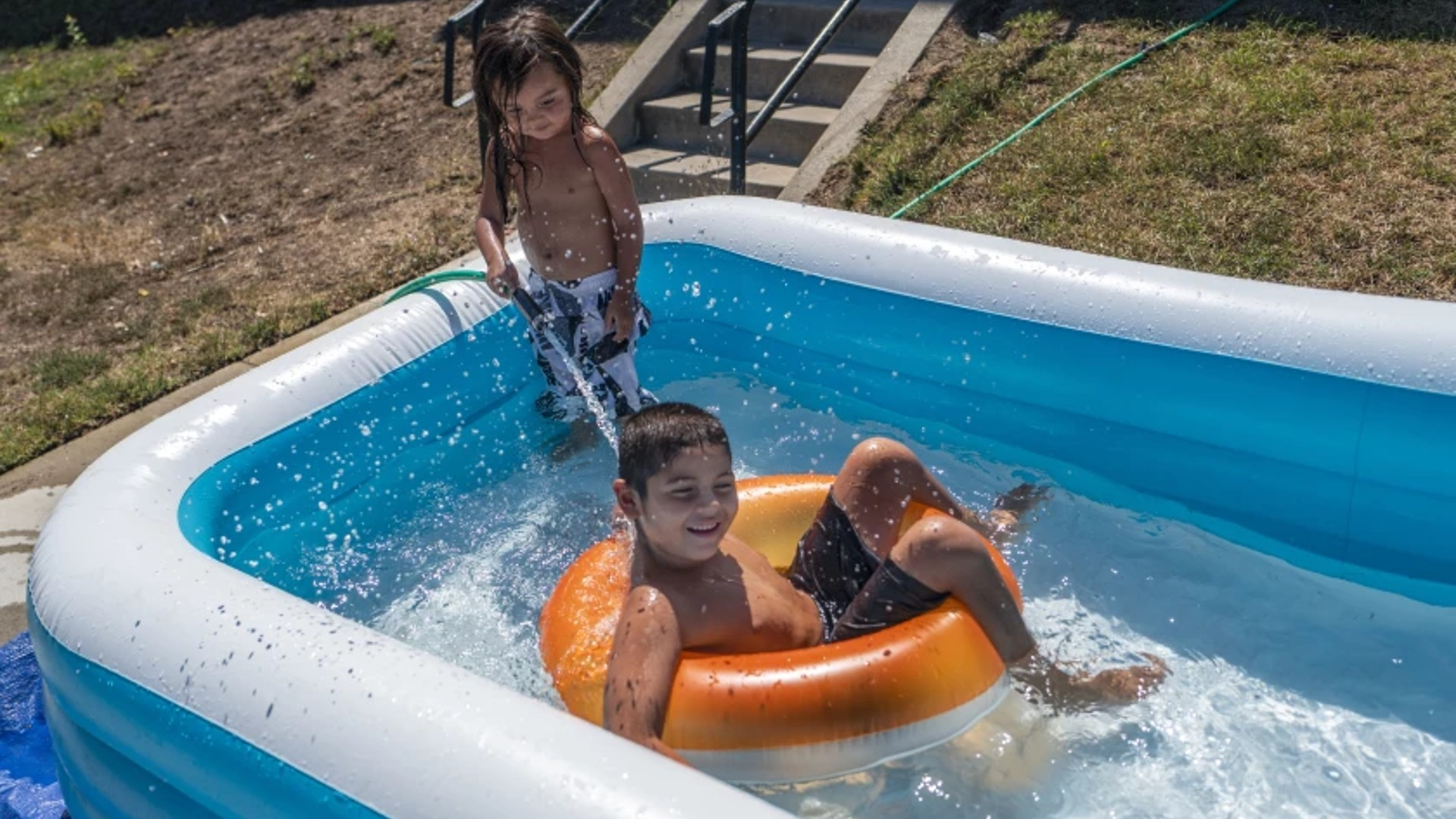 Santonio Trujillo, 3, left, and Adrian Stevens, 7, cool off while playing in a pool in San Pedro on Sept. 5. More warm weather is on tap for the Southland for the next two days.(Francine Orr / Los Angeles Times)