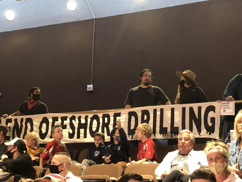 Members of the Surfrider Foundation hold a sign supporting an offshore oil drilling ban at a Huntington Beach City Council meeting on Oct. 19, 2021. (Matt Szabo / Daily Pilot)