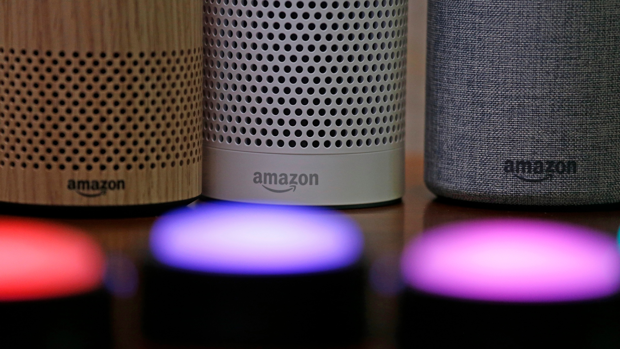 In this Sept. 27, 2017, file photo, Amazon Echo and Echo Plus devices, behind, sit near illuminated Echo Button devices during an event announcing several new Amazon products by the company in Seattle. Users of Amazon's Alexa digital assistant can now request that recordings of their voice commands delete automatically. (AP Photo/Elaine Thompson, File)