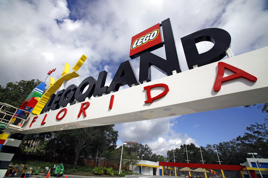 In this Tuesday, Sept. 27, 2011, file photo, a worker puts finishing touches on the entrance sign at Legoland Florida in Winter Haven, Fla. AP Photo/John Raoux, File)